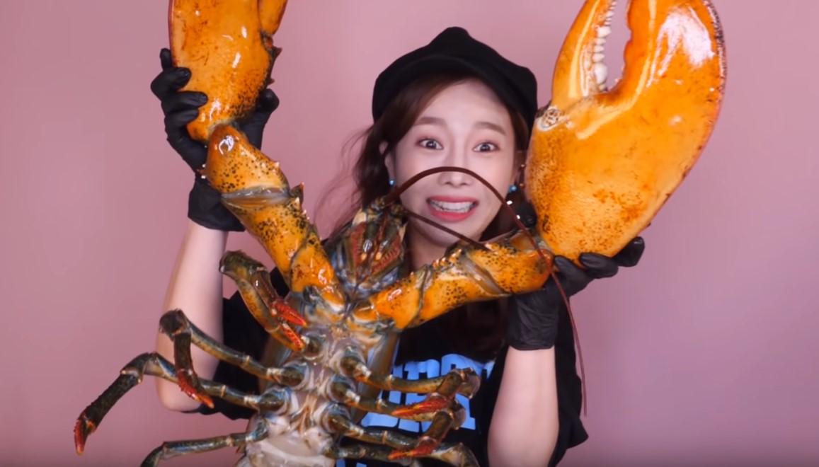 Una asiática comiéndose una langosta gigante